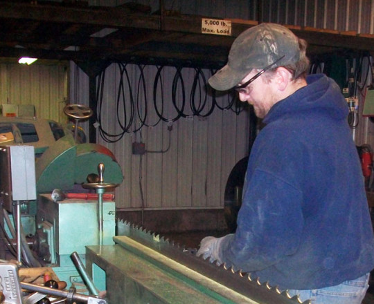Bill Meyer, Head Mechanic, making individual adjustments to the saw blade.