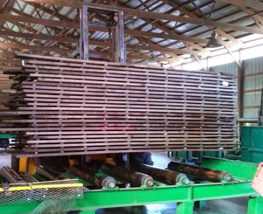 Lumber being moved to off conveyor to await kiln drying.
