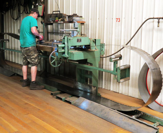Saw work bench; Dustin Nurre, Assistant Mechanic, works on the saws to remove tension and tightness.