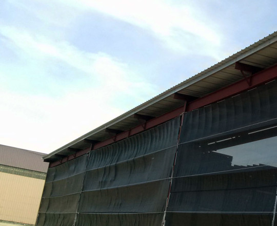 Screen on west side of T-Shed. Allows for controlled air flow and protection from rain.