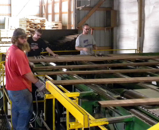 Stick Machine Operator, Travis Rahe, is controlling the speed that the lumber is moving.