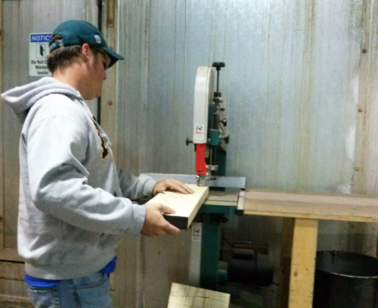 John Carithers, Kiln Operator, testing a piece of lumber from the kiln.