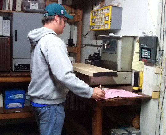 John Carithers, Kiln Operator, performing moisture tests on a piece of lumber from the kiln.